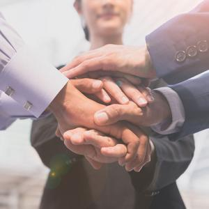 Employees placing hands together